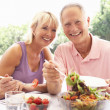 Senior couple eating outdoors — Stock Photo