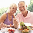 Stock Photo: Senior couple eating outdoors