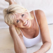 Middle age woman lying down strikes a pose — Stock Photo