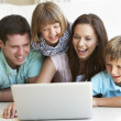 Young parents, with children, on laptop computer - Stock Photo