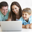 Young parents, with child, on laptop computer — Stock Photo