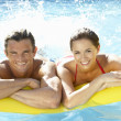 Young couple having fun in pool - Stock Photo
