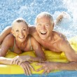 Senior couple having fun in pool - Stock Photo