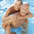 Senior couple having fun in pool — Stock Photo