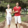 Young couple running through park — Stock Photo