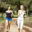 Two young women running in park — Stock Photo #4843972