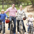 Family enjoying bike ride in park - Stock Photo