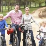 Family enjoying bike ride in park — Stock Photo