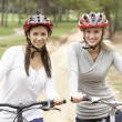 Two Female friends riding bikes in park — Stock Photo
