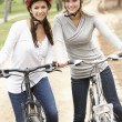 Two Female friends riding bikes in park — Stock Photo #4844007