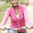 Senior woman riding bicycle in park - Foto Stock