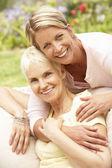 Starší žena a dospělých dcera relaxační v zahradě — Stock fotografie