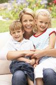 母親と子供たちは庭でリラックス — ストック写真