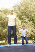 Grandmother And Grandson Jumping On Trampoline In Garden — Stock Photo