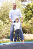 Father And Son Jumping On Trampoline In Garden — Stock Photo