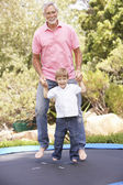 Grandfather And Grandson Jumping On Trampoline In Garden — Stock Photo