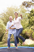 Couple Jumping On Trampoline In Garden — Stock Photo