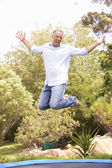Middle Aged Man Jumping On Trampoline In Garden — Stock Photo