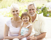 Grandparents And Granddaughter Relaxing In Garden — Stock Photo