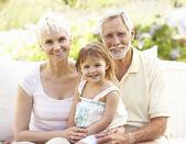 Avós e neta relaxando no jardim — Fotografia Stock