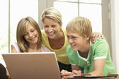 Mother And Teenage Children Using Laptop At Home — Stock Photo