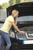 Vrouwelijke bestuurder uitgesplitst op landweg — Stockfoto