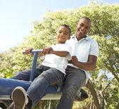 Baba ve oğul tahterevalli park sürme — Stok fotoğraf