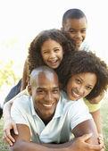 Portret van gelukkige familie opgestapeld in park — Stockfoto
