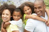 Porträtt av lycklig familj i park — Stockfoto
