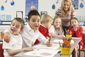 Group Of Primary Schoolchildren And Teacher Working At Desks In — Stockfoto