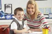 Male Primary School Pupil And Teacher Working At Desk In Classro — Stock Photo