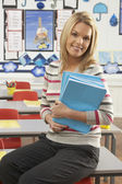 Portrait Of Female Teacher Sitting At Desk In Classroom — Foto de Stock