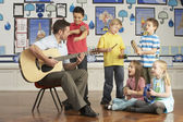Male Teacher Playing Guitar With Pupils Having Music Lesson In C — Stock fotografie