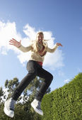 Young Woman Jumping On Trampoline Caught In Mid Air — Stock Photo