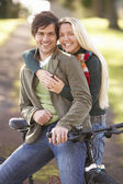Portrait Of Young Couple With Cycle In Autumn Park — Stock Photo