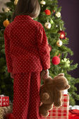 Oung Girl Standing With Teddy Bear In Front Of Christmas Tree — Stock Photo