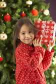 Young Girl Holding Gift In Front Of Christmas Tree — Stock fotografie