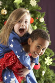 Two Young Children Having Fun In Front Of Christmas Tree — Stock Photo