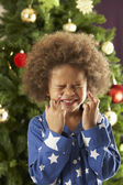 Young Boy Crossing Fingers In Front Of Christmas Tree — Stok fotoğraf