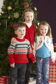 Group Of Young Children With Presents In Front Of Christmas — Stock Photo