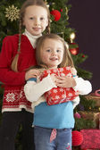 Two Young Girls With Presents In Front Of Christmas Tree — Стоковое фото