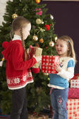 Two Young Girls With Presents In Front Of Christmas Tree — Stok fotoğraf