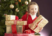 Young Girl Holding Christmas Present In Front Of Christmas Tree — Photo