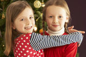 Two Young Girls Hugging In Front Of Christmas Tree — Stock Photo