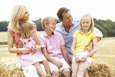 Family Sitting On Straw Bales In Harvested Field — Stock Photo