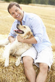 Man Sitting With Dog On Straw Bales In Harvested Field — Stock Photo