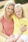 Mother And Daughter Sitting On Straw Bales In Harvested Field — Stock Photo
