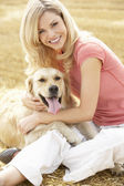 Woman Sitting With Dog On Straw Bales In Harvested Field — Stock Photo