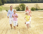 Family Running Together Through Summer Harvested Field — Stock Photo