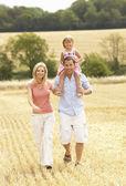 Famille marchant ensemble dans l'été récoltés champ — Photo